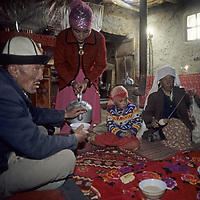 A nomadic Kyrgyz family shares bread and tea while the mother spins wool in their summer house near Lake Karakul, in the Pamir Mountains, Xinjiang, China.