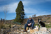 Welsh sheep farmer Howell Williams and his sheep dog Ben sit by the entry point to the farms 15kW hydro power plant on the Brecon Beacons, Wales.