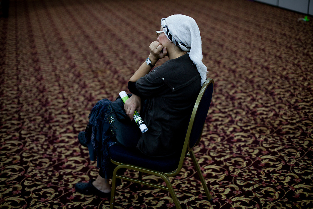 """A follower of the late Rabbi Meir Kahane, founder of both the Jewish Defense League (JDL) and """"Kach"""", an Israeli political party, sits a listens to speakers, during a rally in Jerusalem on October 26, 2010, marking the 20th anniversary of his death after he was assassinated by an Arab gunman in a Manhattan hotel in November 1990."""