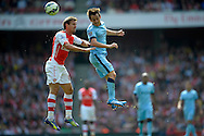 Arsenal's Nacho Monreal (l) and Manchester City's David Silva challenge for a header . Barclays Premier league match, Arsenal v Manchester city at the Emirates Stadium in London on Saturday 13th Sept 2014.<br /> pic by John Patrick Fletcher, Andrew Orchard sports photography.