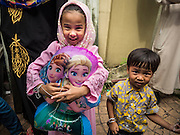 17 JULY 2015 - BANGKOK, THAILAND:     A girl holds her Disney character balloon after Eid services at Ton Son Mosque in Bangkok. Eid al-Fitr is also called Feast of Breaking the Fast, the Sugar Feast, Bayram (Bajram), the Sweet Festival or Hari Raya Puasa and the Lesser Eid. It is an important Muslim religious holiday that marks the end of Ramadan, the Islamic holy month of fasting. Muslims are not allowed to fast on Eid. The holiday celebrates the conclusion of the 29 or 30 days of dawn-to-sunset fasting Muslims do during the month of Ramadan. It's common to give children small gifts and toys, like helium balloons, for Eid. Islam is the second largest religion in Thailand. Government sources say about 5% of Thais are Muslim, many in the Muslim community say the number is closer to 10%.          PHOTO BY JACK KURTZ