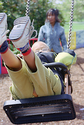 Single mother pushing young son on swing in playground,
