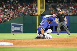 May 22, 2018 - Arlington, TX, U.S. - ARLINGTON, TX - MAY 22: Texas Rangers first baseman Ronald Guzman (67) grabs the baseball and slides to a stop during the game between the Texas Rangers and the New York Yankees on May 22, 2018 at Globe Life Park in Arlington, Texas. The Rangers defeat the Yankees 6-4. (Photo by Matthew Pearce/Icon Sportswire) (Credit Image: © Matthew Pearce/Icon SMI via ZUMA Press)