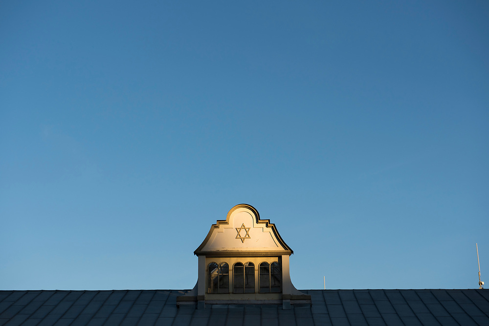 Kaunas, Lithuania - August 15, 2015: Sunlight from the setting sun illuminates a Star of David on the Kaunas Synagogue, a Neo-Baroque synagogue built in 1872 in Kaunas, Lithuania. Clear sky provides copyspace