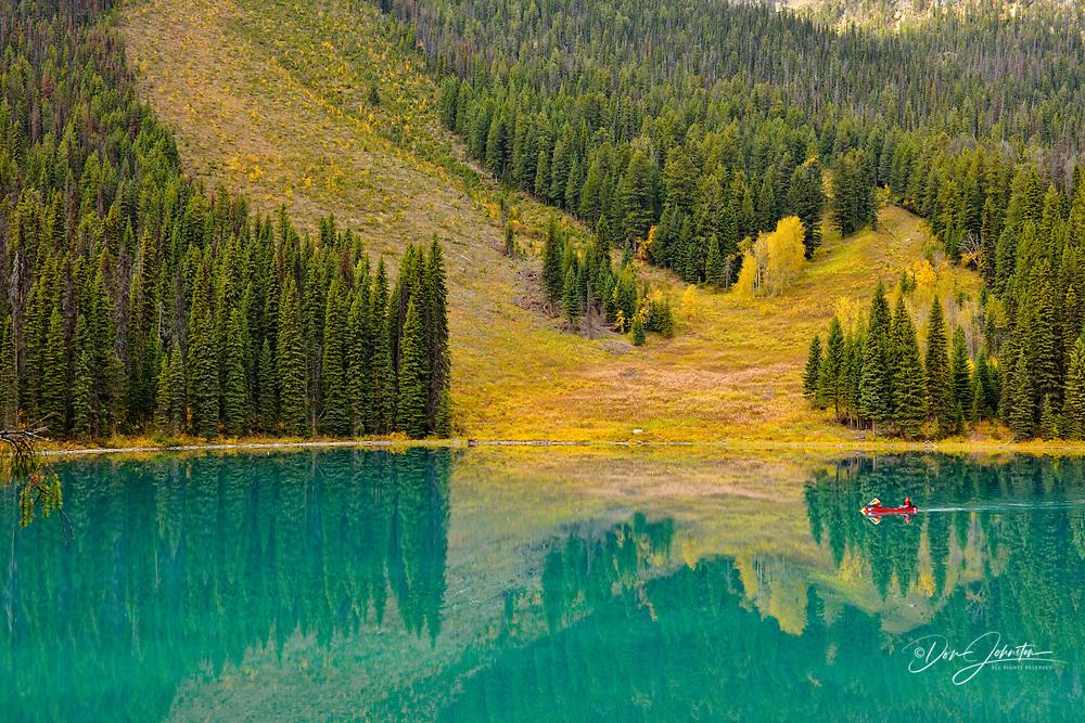Emerald Lake with tourists paddling a canoe, Yoho National Park, Alberta, Canada