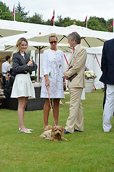 Left to right, AGNIESZKA BUTTER, LADY VICTORIA HERVEY and CHARLIE BUTTER at the Cartier Queen's Cup Polo final at Guard's Polo Club, Smiths Lawn, Windsor Great Park, Egham, Surrey on 14th June 2015