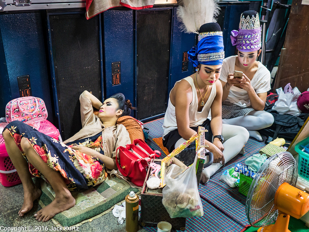 """30 JANUARY 2016 - NONTHABURI, NONTHABURI, THAILAND: Likay performers wait to go on stage during a """"likay"""" show at Wat Bua Khwan in Nonthaburi, north of Bangkok. Likay is a form of popular folk theatre that includes exposition, singing and dancing in Thailand. It uses a combination of extravagant costumes and minimally equipped stages. Intentionally vague storylines means performances rely on actors' skills of improvisation. Like better the known Chinese Opera, which it resembles, Likay is performed mostly at temple fairs and privately sponsored events, especially in rural areas. Likay operas are televised and there is a market for bootleg likay videos and live performance of likay is becoming more rare.     PHOTO BY JACK KURTZ"""