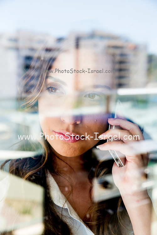 Frustrated young business woman reflects in her office window as she talks on a mobile phone