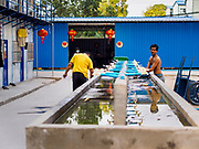 """12 FEBRUARY 2019 - SIHANOUKVILLE, CAMBODIA: A Chinese construction worker washes up in a Chinese workers' labor camp in Sihanoukville. There are about 50 Chinese casinos and resort hotels either open or under construction in Sihanoukville. The casinos are changing the city, once a sleepy port on Southeast Asia's """"backpacker trail"""" into a booming city. The change is coming with a cost though. Many Cambodian residents of Sihanoukville  have lost their homes to make way for the casinos and the jobs are going to Chinese workers, brought in to build casinos and work in the casinos.      PHOTO BY JACK KURTZ"""