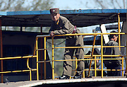 A North Korean soldier looks out at a Chinese boat from the border town of Sunuiju October 11, 2006. DPRK, north korea, china, dandong, border, liaoning, democratic, people's, rebiblic, of, korea, nuclear, test, rice, japan, arms, race, weapons, stalinist, communist, kin jong il