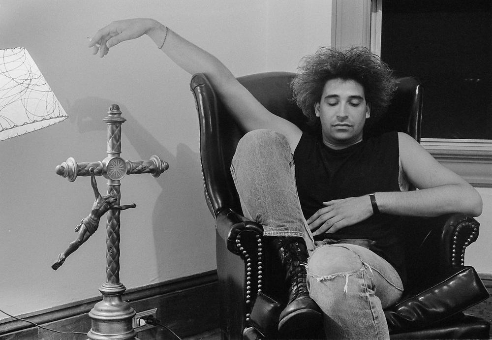 Man in leather chair with cigarette next to broken crucifix statue (late 1980's)