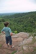 Teenage boy standing on high cliff looking over Ebbor Gorge, Mendip Hills, Somerset, England