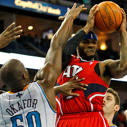 January 29, 2012; New Orleans, LA, USA; Atlanta Hawks power forward Josh Smith (5) is defended by New Orleans Hornets center Emeka Okafor (50) and power forward Jason Smith (14) during the second half of a game at the New Orleans Arena. The Hawks defeated the Hornets 94-72.  Mandatory Credit: Derick E. Hingle-US PRESSWIRE
