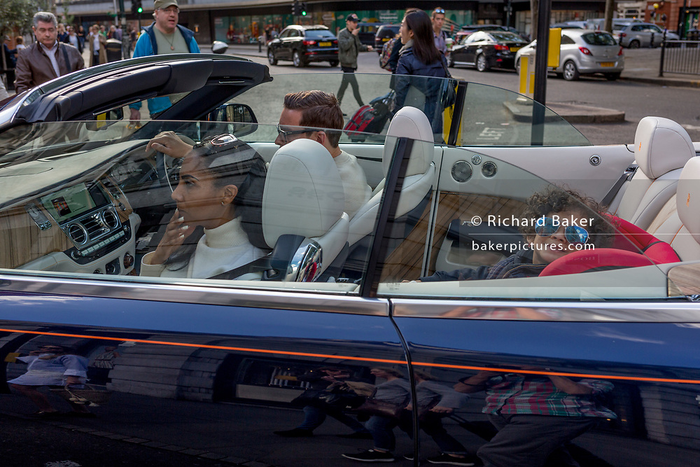 Wealthy adults and a child wearing sunglasses who smiles in the back of an open-top car remaining stationary at traffic lights in Sloane Square, on 14th May 2017, in London, England.