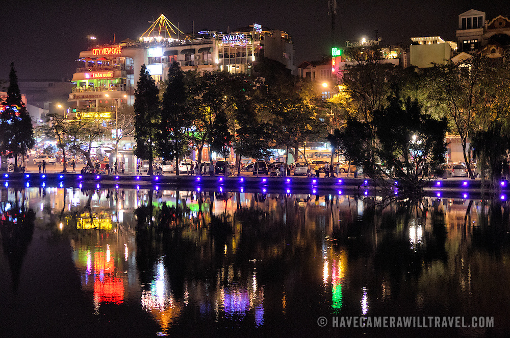 The lights of Hanoi's Old Quarter reflected on Hoan Kiem Lake (Ho Hoan Kiem) at night. The lake's wall at this end is ringed with spotlights that change color. Behind are the lights from tourist bars and restaurants with a view out over the lake.