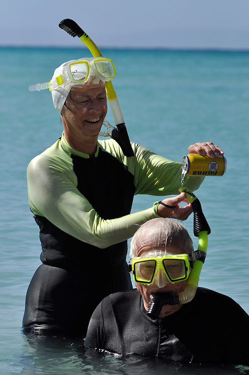 Woman pouring beer down her partner's snorkel, Sea of Cortez, Baja California, Mexico.