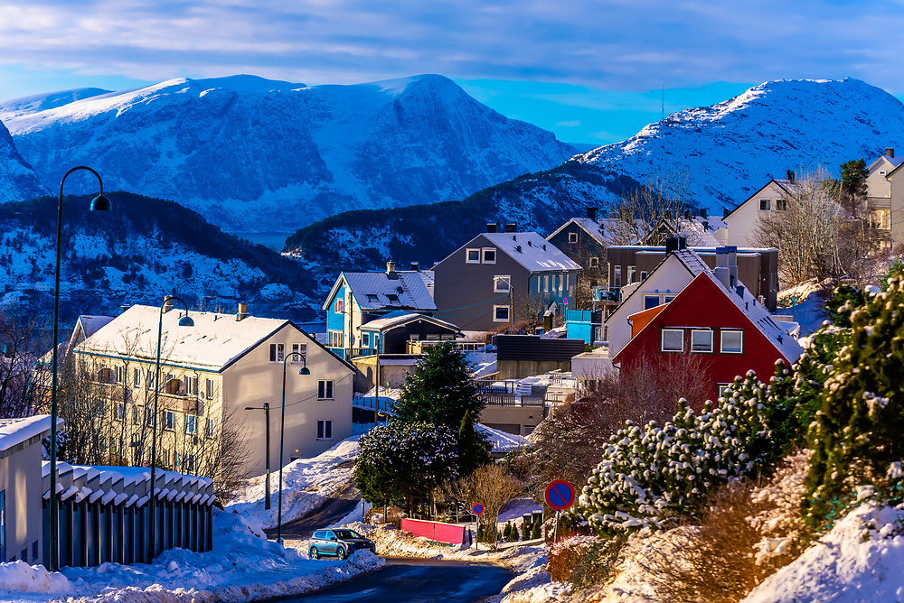 A winter scene of houses ringed by snowcapped mountains in Alesund, Norway. The town is famous for its art nouveau (Jugendstil) architecture. The  town was rebuilt after a fire in 1904. Alesund is in the heart of Fjord Country, at the entrance to Geirangerfjord on Norway's west coast.