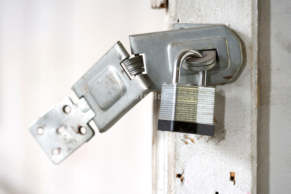 close up of broken open door doorpost with a new padlock