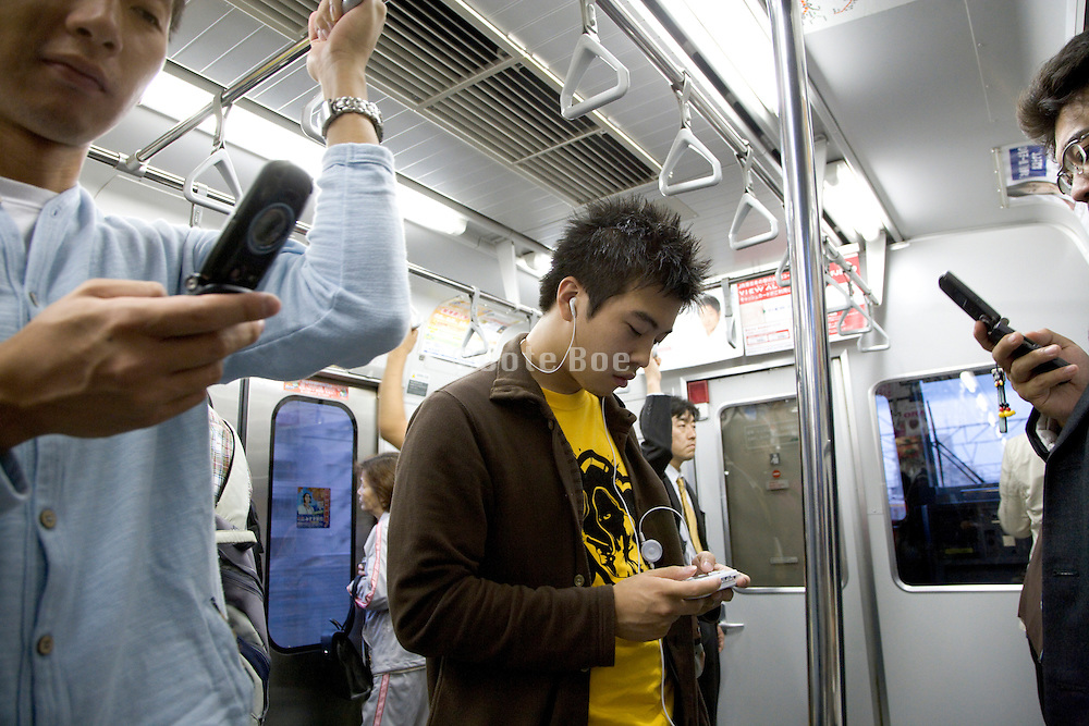 young Japanese teenagers text messaging while traveling on the train