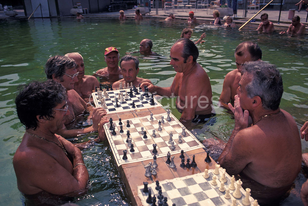 Hungarian gentlemen play chess in the thermal healing spa waters of Budapests famous Szechenyi thermal bath, on 18th June 1990, in Budapest, Hungary. Budapest is especially known for its spas. The Széchenyi Medicinal Bath  Szechenyi-gyogyfurdo is the largest medicinal bath in Europe. Its water is supplied by two thermal springs, their temperature is 74°C/165°F and 77°C/171°F, respectively. The bath can be found in the City Park, and was built in 1913 in Neo-baroque style to the design of Gyozo Czigler.