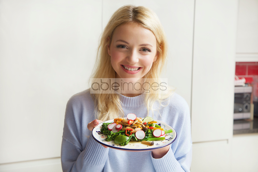 Smiling Woman Holding Plate with Stir Fry