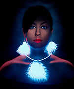Portrait of a young woman wearing glowing feather ear rings and a glowing feather necklace necklace.Black light