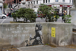 "© Licensed to London News Pictures. 27/04/2019. LONDON, UK.  An artwork has appeared on a wall at Marble Arch following ten days of protests in London by Extinction Rebellion, a group demanding that governments take action to tackle climate change.  Now covered in a protective plastic cover, the artwork has been attributed to the celebrated street artist Banksy and depicts an image of a plant and a girl holding a gardening tool with the Extinction Rebellion logo on it next to the text ""From this moment despair ends and tactics begin"".  Photo credit: Stephen Chung/LNP"