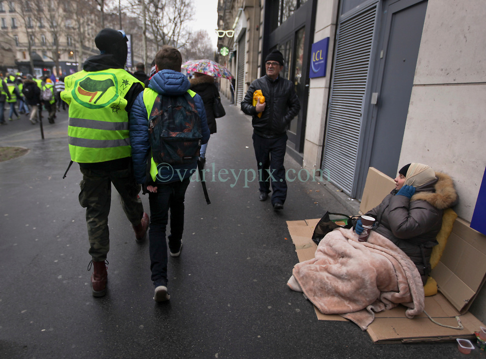 19 January 2019. Paris, France.<br /> Gilets Jaunes - Acte X take to the streets of Paris. A homeless person watches the marchers pass by. An estimated 7,000 people took part in the looping 14 km route from Place des Invalides to protest tax hikes from the Government of Emmanuel Macron imposed on the people. An estimated 80,000 people took part in protests across the country. Regrettably the movement has attracted a violent element of agitators who often face off with riot police at the end of the marches which tends to deflect attention away from the message of the vast majority of peaceful protesters.<br /> Photo©; Charlie Varley/varleypix.com