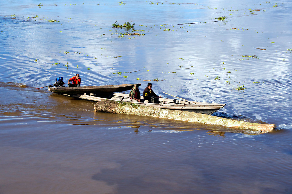 A boat tows another boat down a river past a large log. Photo by Adel B. Korkor.