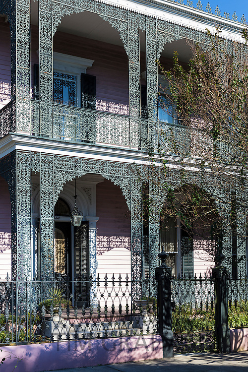 Grand mansion house with ornate lacy wrought iron fretwork double gallery in the Garden District of New Orleans, Louisiana, USA