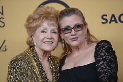 December 27, 2016 - File - CARRIE FRANCES FISHER (October 21, 1956 - December 27, 2016) was an American actress, screenwriter, author, producer, and speaker. She was known for playing Princess Leia in the Star Wars films. Fisher was also known for her semi-autobiographical novels, including Postcards from the Edge, and the screenplay for the film of the same name, as well as her autobiographical one-woman play, and its nonfiction book, Wishful Drinking, based on the show. Her other film roles included Shampoo (1975), The Blues Brothers (1980), Hannah and Her Sisters (1986), The 'Burbs (1989), and When Harry Met Sally (1989). Pictured: Jan. 25, 2015 - Los Angeles, California - Carrie Fisher and Debbie Reynolds.  Reynolds was honored with the Life Achievement Award.  pose backstage at the 21st Annual Screen Actors Guild Awards at the Shrine Auditorium in Los Angeles, California on Sunday January 25, 2014. (Credit Image: © Andy Holzman/Los Angeles Daily News/ZUMA Wire)