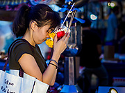 05 MARCH 2019 - BANGKOK, THAILAND:  A woman who works in the Ratchada Night Market prays before starting her shift. The Ratchada Night Market is the newest night market in Bangkok. It was originally a small night market popular with local people but now is tourism destination. Most nights the market is jammed with foreign tourists.    PHOTO BY JACK KURTZ