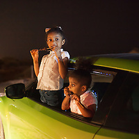 In the cool of the night girls eat kebabs in their father's car on the beach on the Gulf of Oman in Muscat.