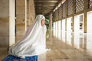 Muslim woman having a moment of quiet contemplation in a mosque.