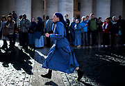 A nun runs to the pre-conclave mass in St. Peter's Square during the first day of conclave and the selection of the new Pope in Vatican City, March 12, 2013. Photograph by Todd Korol