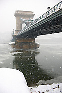 South  side of yhe Szechenyi Lanchid (Chain Bridge) in the winter snow looking towards the castle district. Budapest Hungary stock photos. .<br /> <br /> Visit our HUNGARY HISTORIC PLACES PHOTO COLLECTIONS for more photos to download or buy as wall art prints https://funkystock.photoshelter.com/gallery-collection/Pictures-Images-of-Hungary-Photos-of-Hungarian-Historic-Landmark-Sites/C0000Te8AnPgxjRg