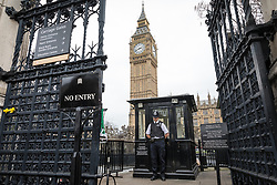 © Licensed to London News Pictures. 29/03/2017. London, UK. A policeman stationed at the entrance to Parliament bows his head during a minute's silence held at 14:40, exactly one week after Khalid Masood began a terrorist attack on Westminster on 22 March 2017. PC Keith Palmer was killed by the attacked after he entered Carriage Gate. Photo credit: Rob Pinney/LNP
