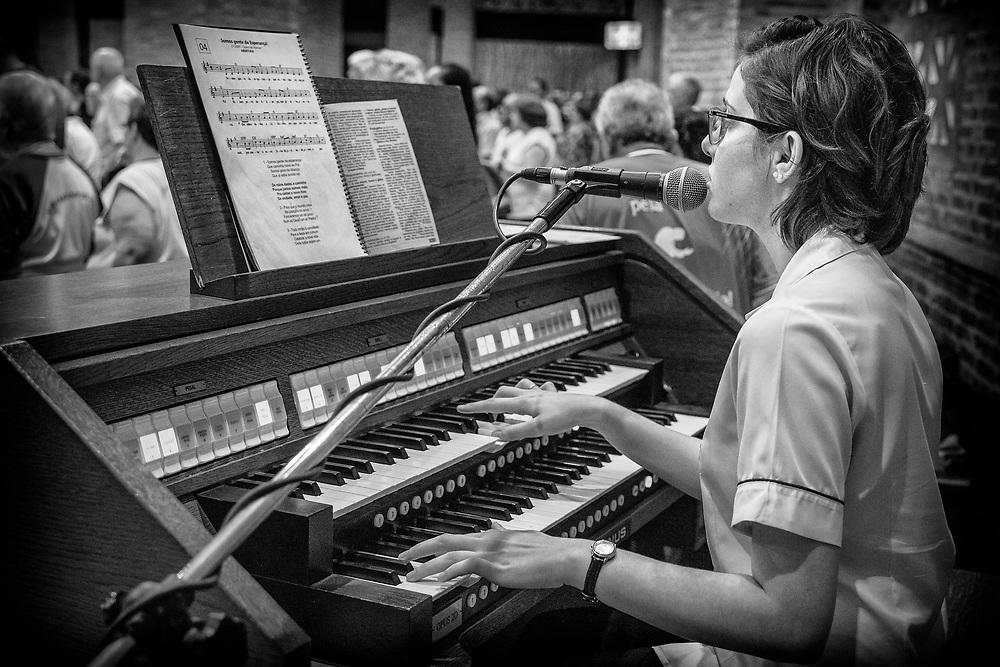 Organista do Santuário tocando e cantando durante a missa.