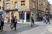 A man skateboards down Brick Lane as people cross the road. London, United Kingdom.