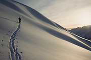 Alaska. Kenai Peninsula. Turnagain Pass. Tin Can Mt. Backcountry skier crossing south face at sunrise.