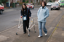 Single parent with her daughter in a frame walking down a street together,