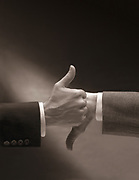 Close up of businessmen's hands in front of one another with thumbs up and thumbs down