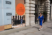A lady wearing a distinctive blue dress walks past a board showing a man wearing a similar colour shade at the Alpheus Building on Blomfield Street, a property being refurbished near Liverpool Street Station in the City of London, the capital's financial district - aka the Square Mile, on 8th August, in London, England. The address at 31–35 Blomfield Street is a modern retail space behind a historic Edwardian facade.
