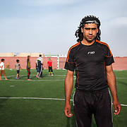 Faysal, 30, and his family arrived at Azraq camp last July from Damascus. He's wearing his Shmagh (head scarf), which he holds onto dearly. His good friend who died in the Syrian conflict gave it to him.<br /> <br /> Faysal teaches boys soccer in one of Mercy Corps' adolescent friendly spaces in Azraq camp for Syrian refugees, Jordan, May 2015.