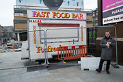 Lunch outside a fast food bar closed off during redevelopment of the Aldgate area in London, England, United Kingdom.