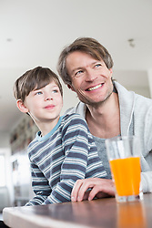 Father and son looking away, smiling