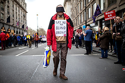 "© Licensed to London News Pictures. 23/03/2019. London, UK. A main wears a blindfold and a placard which reads ""Say No to Blind Brexit"" as hundreds of thousands of people march through central London to demand that government allow a ""People's Vote"" on the Brexit deal. Several key votes will be held in Parliament in the coming week. Photo credit: Rob Pinney/LNP"