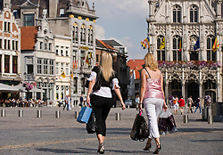 Pedestrians and bicyclists make their way past the ornate city hall building on the Grote Markt or city square, in Mechelen, Belgium on Thursday, Sept. 11,2008.  (Photo © Jock Fistick)