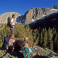 A family rests during a hike in Big Pine Canyon, part of John Muir Wilderness in California's Sierra Nevada.  Left to Right in the background are Slide Mountain, Temple Crag, Mount Gayley and Mount Sill.  The Palisade Glacier is just visible on far upper right.
