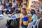 """26 SEPTEMBER 2014 - PATTAYA, CHONBURI, THAILAND: Tourist police process """"katoeys"""" or Ladyboys, (the Thai term for a transgendered prostitute) on Walking Street in Pattaya. Pataya, a beach resort about two hours from Bangkok, has wrestled with a reputation of having a high crime rate and being a haven for sex tourism. After the coup in May, the military government cracked down on other Thai beach resorts, notably Phuket and Hua Hin, putting military officers in charge of law enforcement and cleaning up unlicensed businesses that encroached on beaches. Pattaya city officials have launched their own crackdown and clean up in order to prevent a military crackdown. City officials have vowed to remake Pattaya as a """"family friendly"""" destination. City police and tourist police now patrol """"Walking Street,"""" Pattaya's notorious red light district, and officials are cracking down on unlicensed businesses on the beach.     PHOTO BY JACK KURTZ"""